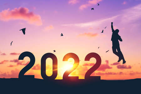 Silhouette man jumping and birds flying on sunset sky at top of mountain and number 2022 abstract background. Happy new year and holiday celebration concept. Vintage tone filter color style.