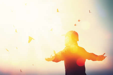 Freedom feel good and travel adventure concept. Copy space of silhouette man rising hands on sunset sky at top of mountain and bird fly abstract background. Vintage tone filter effect color style. Banque d'images