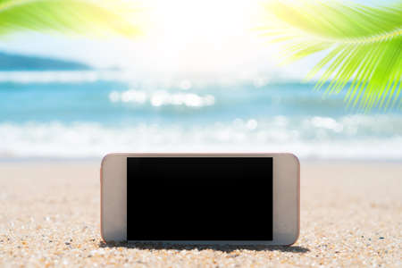 Smart phone on tropical sand beach with palm leaf and bokeh sunlight wave abstract background. Black copy space of technology and travel nature concept. Vintage tone filter effect color style. Stock Photo