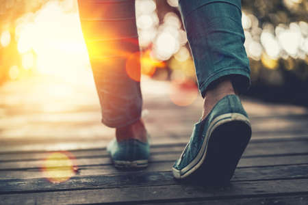 Close up woman walk in to the wild with sunset and sunlight background. Travel adventure and freedom concept. Vintage tone filter effect color style. Stock Photo