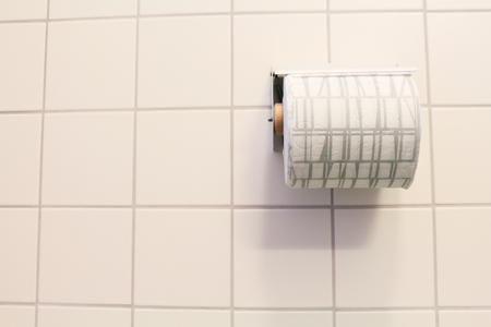 bathroom wall: bathroom tissue on anthracite tiled wall.