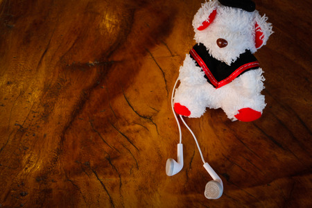 Earphone white and Dolly bears on wood Background.
