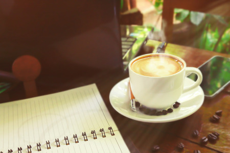 Cup of cappuccino with newspaper on the table, coffee shop background, warm tone. Stock Photo