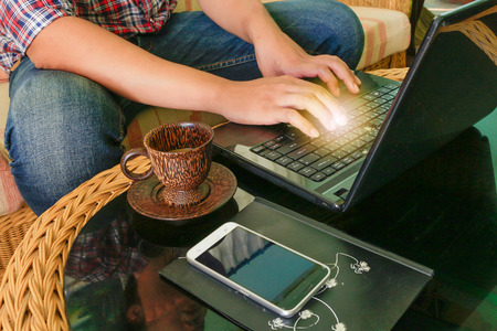 Businessman using laptop with table and telephone on rattan table in the house with calculator and a cup of coffee.