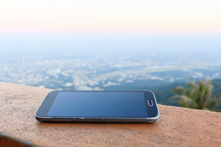 Mobile Phone on wood, City and mountain Background.