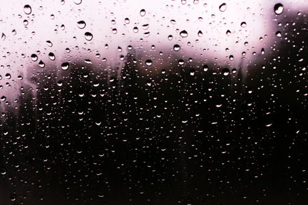Textures of water droplets of rain flow down the windowpane. Rain drop on the car glass background, Blurred photo, Soft focus