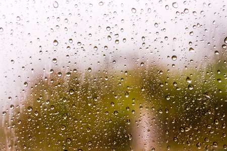 Textures of water droplets of rain flow down the windowpane. Rain drop on the car glass background, Blurred photo, Soft focus 스톡 콘텐츠