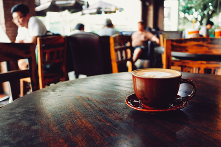Latte coffee cup on wooden table in cafe Banque d'images
