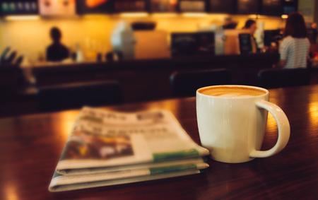 Café con leche en la cafetería con patrón de corazón en una taza blanca sobre la mesa de madera en el fondo del café Foto de archivo