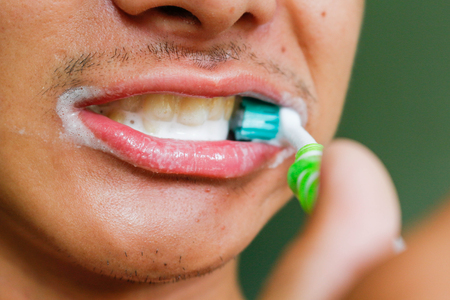 Dental hygiene - young man holding toothbrush and brushing teeth