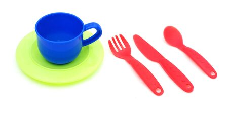 Plastic cup, spoon, knife anf fork, against a white background
