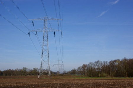 Powerlines in agricultural landscape against a blue sky Stock Photo