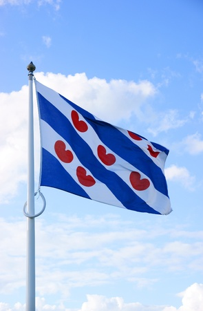 Flag of dutch provence Friesland, blowing in the wind,against a blue sky