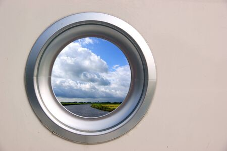 Porthole of a boat with nice view on a scenic landscape Stock Photo