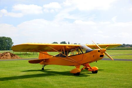 Small vintage yellow airplane on a grasfield Stock Photo