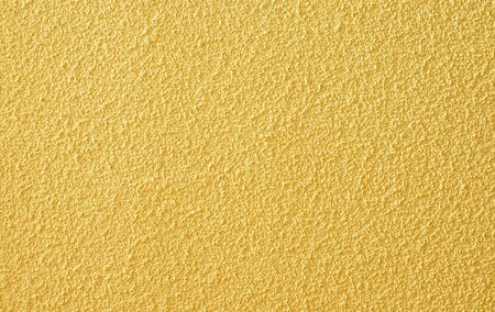Yellow grainy background as used on walls Stock Photo