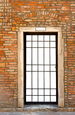 Metal bar door in old brick wall, isolated on white