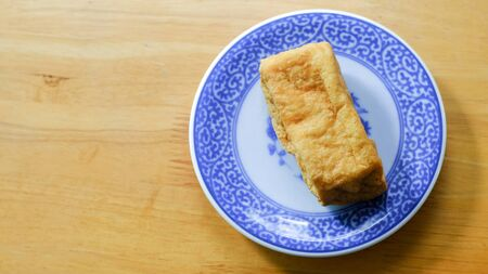 russian cuisine: Fried bean curd in blue chinese dish on wooden table