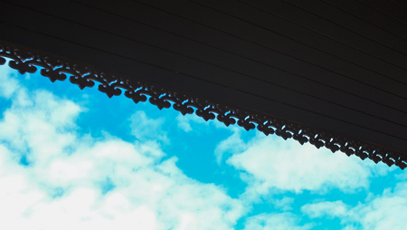 Silhoulette perforated wooden for roof with vivid sky behind Stock Photo