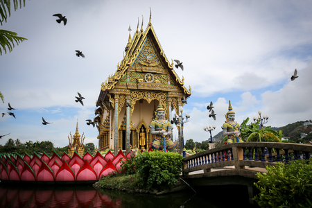 The Thai temple in Wat Plai Laem in Samui Island Thailand, in the middle of the water, contains giant statues and elephants.Pigeon flies through. Stock fotó