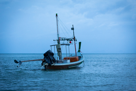 Thai fishing boat parked in the sea evening blue sky.