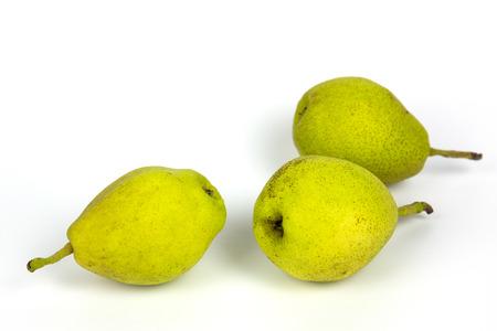 Fresh pears, three yellow fruit on white background.