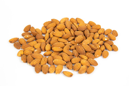 Pile of almonds seeds on white background.