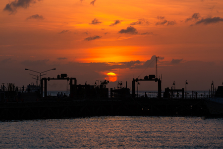 Suratthani, Thailand - January 7, 2019: Sunset in the sea at Nathon The ferry pier has tourists to sit on the pier. Big sun Beautiful orange sky at Koh Samui Southern Thailand on the January 7, 2018 in Samui Island, Suratthani, Thailand. Banco de Imagens