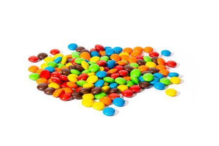 Colorful chocolate MMs in and out of focus on white background Banco de Imagens