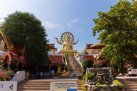 SAMUI, THAILAND - JAN 9 : Scene in Wat Phra Yai (Big buddha temple) in Samui island with tourists under blue sky in Samui island, Thailand, on Jan 9, 2020.