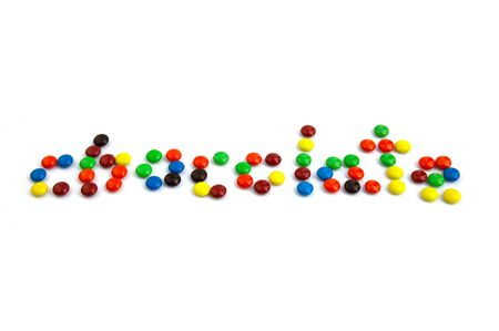 Colorful chocolate M&Ms in and out of focus on white background.
