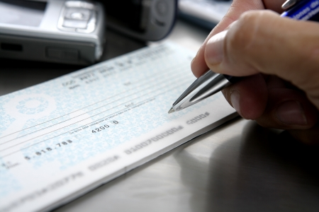 signing document: Firmar un cheque. Sign a bank check