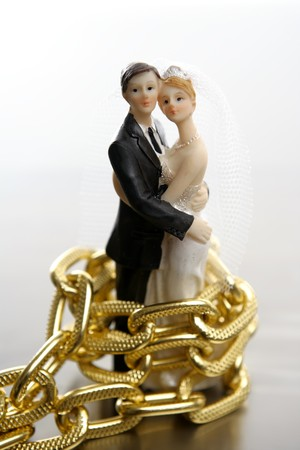 aniversary: Metaphor of marriage as a loss of freedom. Wedding figurines and golden chain