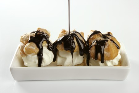 addictive: Delicious and addictive cream puff cake dessert with chocolate syrup Stock Photo