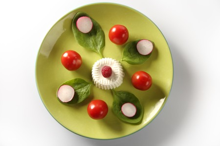 varied: Salad in green dish with tomato, radish and fresh cheese