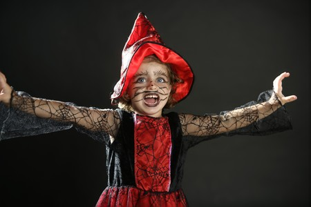 Toddler beautiful witch girl wearing halloween costume and make up photo