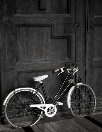 vintage door: Aged vintage black bicycle, big wooden door, black and white
