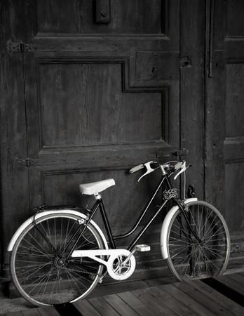 Aged vintage black bicycle, big wooden door, black and white