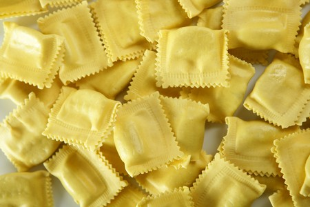 Cheese filled Italian yellow pasta texture, white background photo