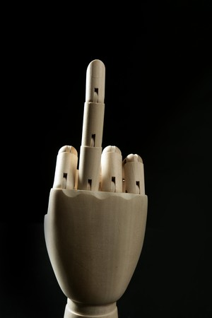 Dirty expression with middle finger up in wooden mannequin hand photo
