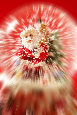 Santa claus figurine on a glass snowing ball, red background studio shot photo