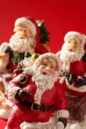 Three Santa Claus figurines over red background, studio shot photo