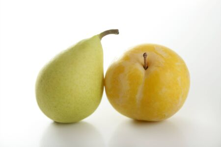 yellowish: Close up of yellow Mirabelles and Pear on white studio background