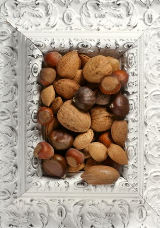 wooden decorated classic white frame, varied nuts inside photo