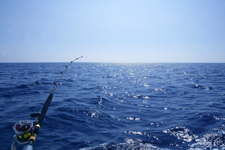 Fishing on the boat with trolling rod and reel. Blue Mediterranean sea. Stock Photo