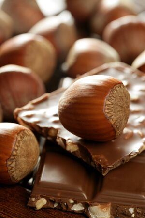 Hazelnuts and chocolate on brown wood enviroment at studio photo