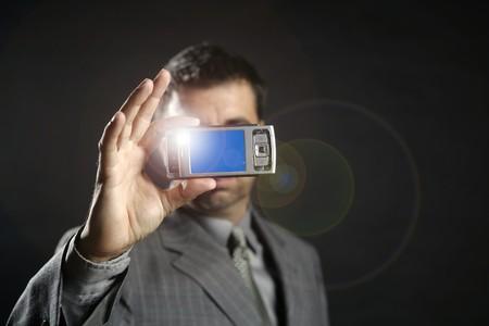 Businessman taking photos, mobile camera, black background Stock Photo - 4097060
