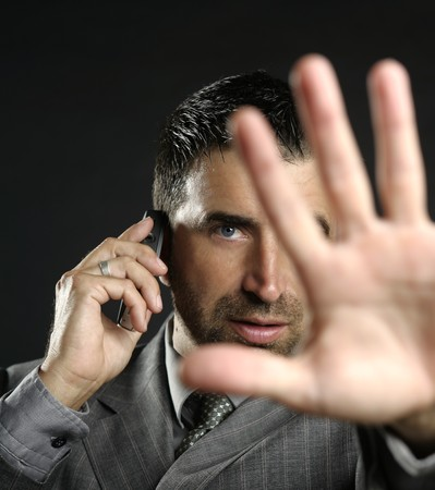 no signal: Angry businessman saying stop with hand,talking to a mobile phone Stock Photo