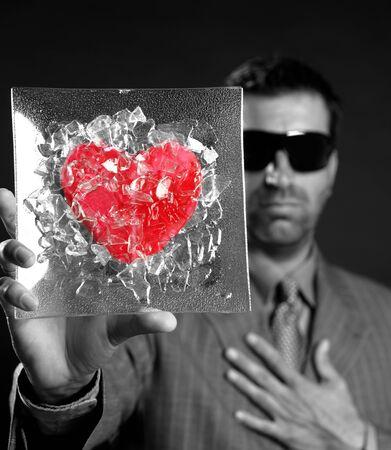 Broken red glass heart businessman metaphor, black background studio shot photo