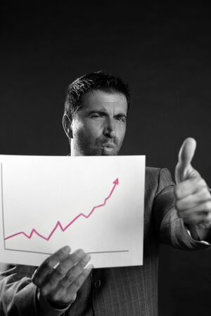 Businessman with good sales reports graph, studio shot black background photo